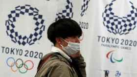 Un joven japonés con mascarilla, delante del logo de Tokio 2020