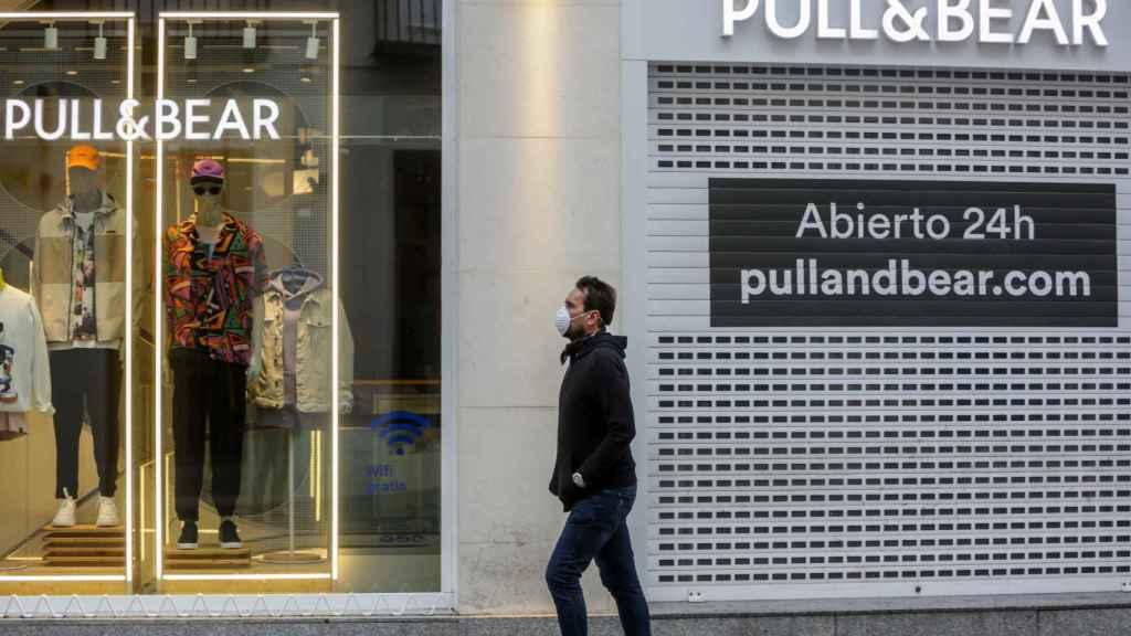 Una persona con mascarilla camina frente a una tienda cerrada y vacía.