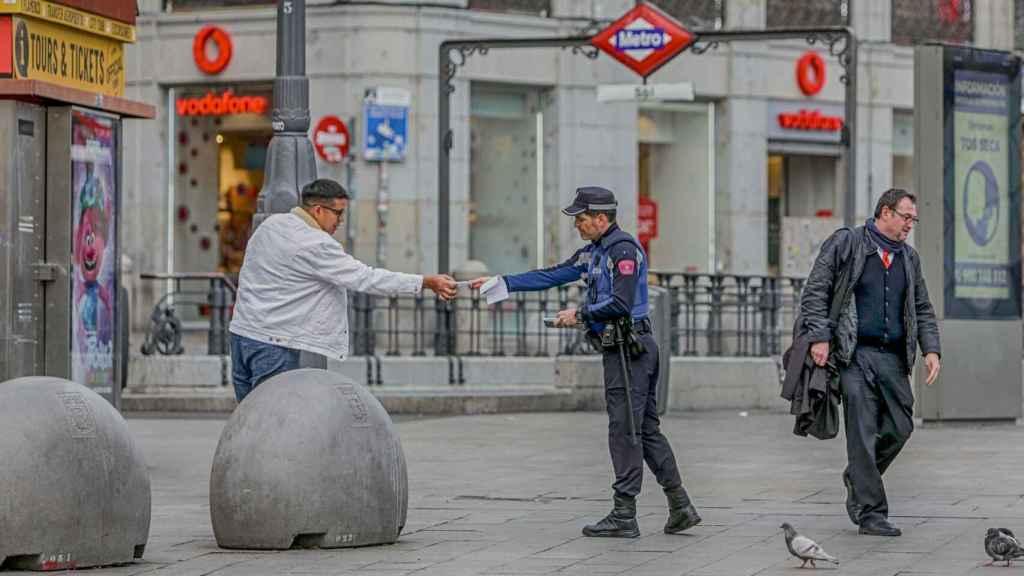 Un persona siendo multada por no cumplir los requisitos de movilidad durante el estado de alarma.