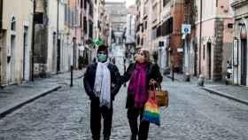 Una pareja camina por una calle desierta en Roma