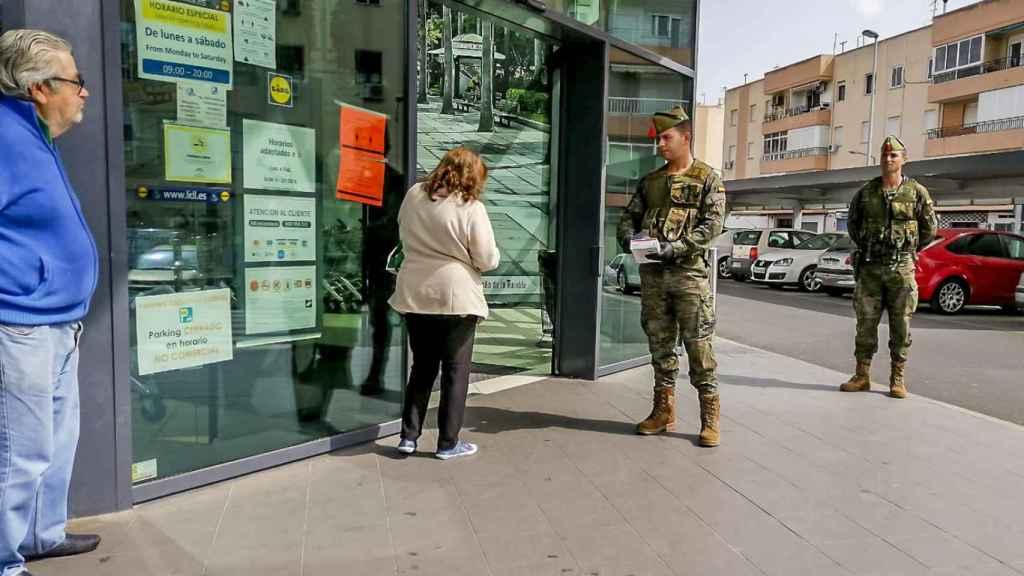 Un legionario charla con una señora en una calle de un municipio andaluz.