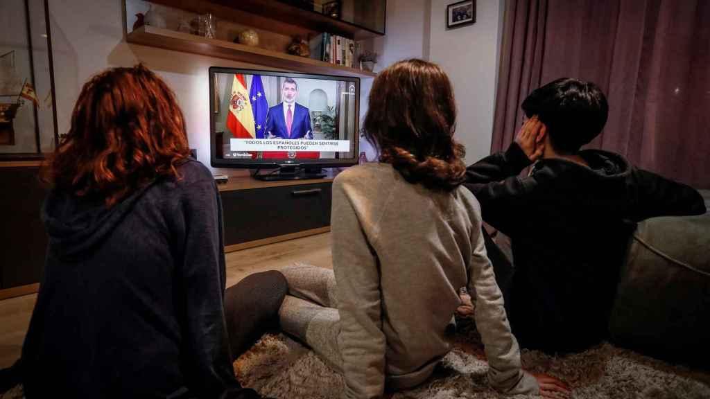 Tres personas ven el discurso extraordinario del rey Felipe VI.