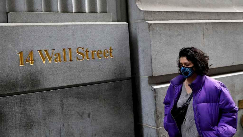 Una mujer lleva una mascarilla en su paseo por Wall Street.