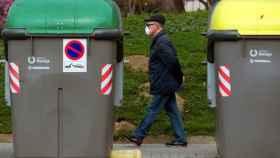 Un hombre con una mascarilla pasea por el centro de Barcelona junto a unos contenedores.