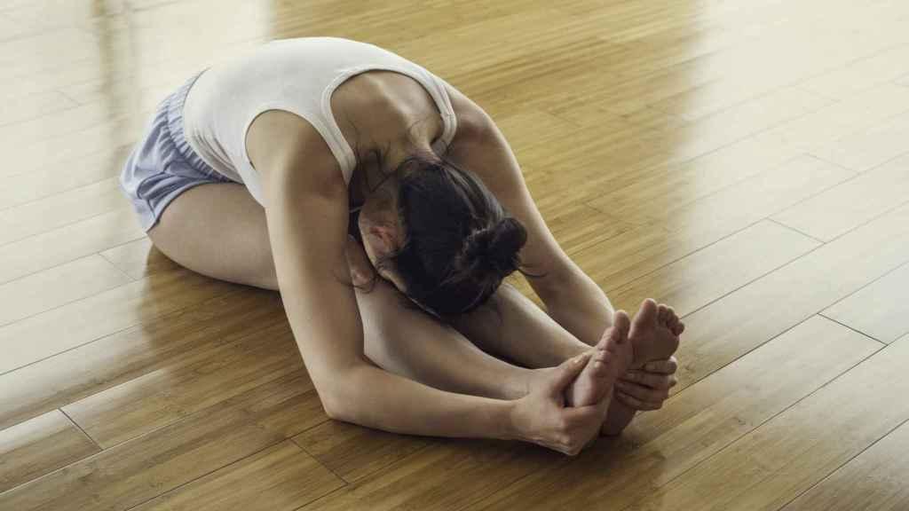 Imagen de archivo de una persona haciendo estiramientos en el suelo.