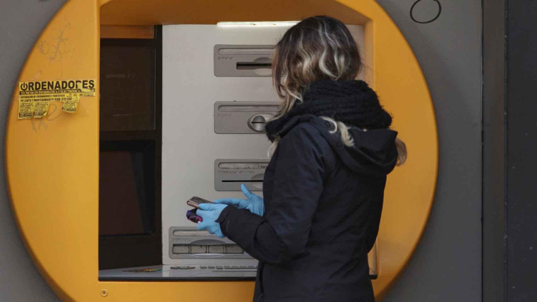 Mujer sacando dinero del cajero en imagen de archivo.
