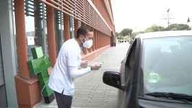 Una farmacia en Torre (Sevilla), permite recoger medicamentos desde los coches para evitar el contacto. En imagen, el farmacéutico entregando el producto.