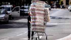 Un hombre compra rollos de papel higiénico en un supermercado.
