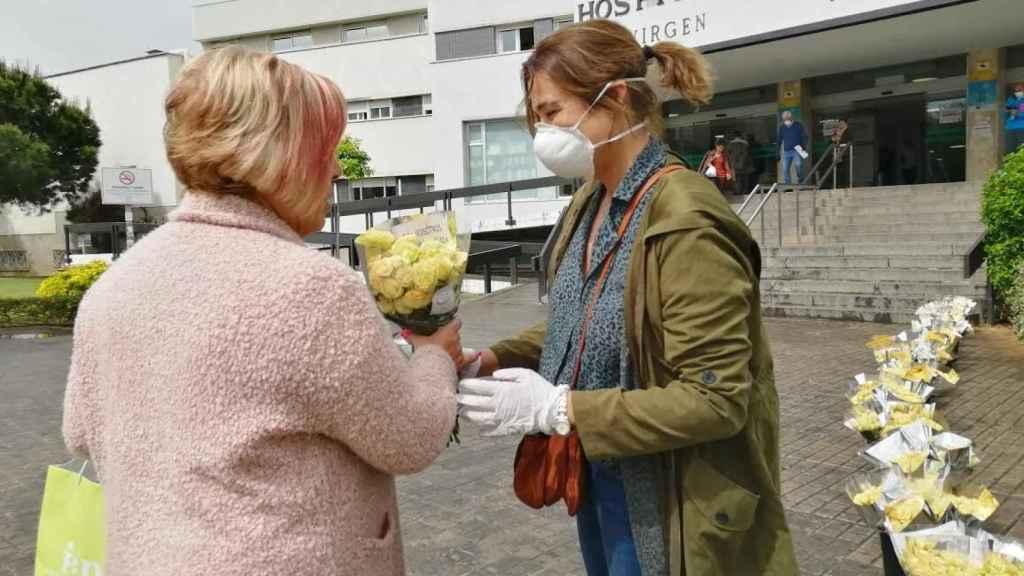 Rocío Gómez (derecha), regala un ramo de rosas de pitiminí a la sanitaria Dolores Ubri, este viernes, en Sevilla.