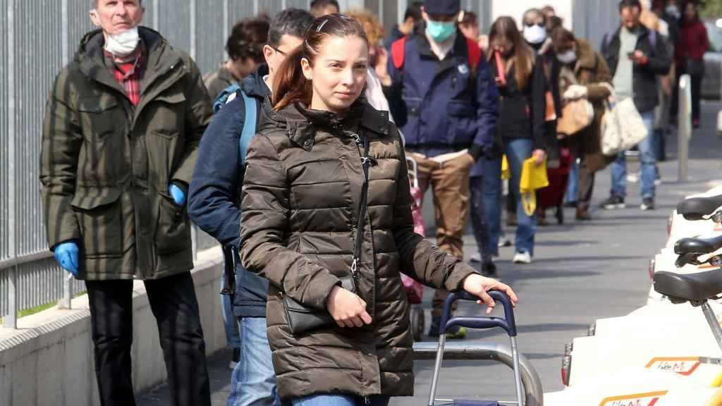 Ciudadanos italianos hacen cola para entrar a un supermercado.