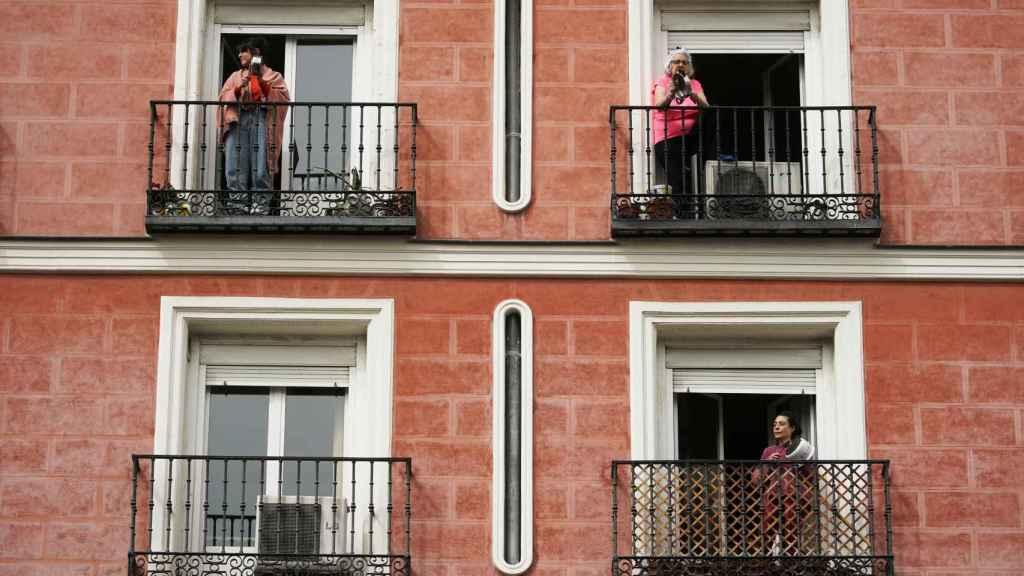 Varias mujeres, con sus cacerolas, en los balcones de sus casas.