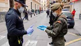 Un policía local de Murcia ofrece gel desinfectante a una militar del Ejército de Tierra.