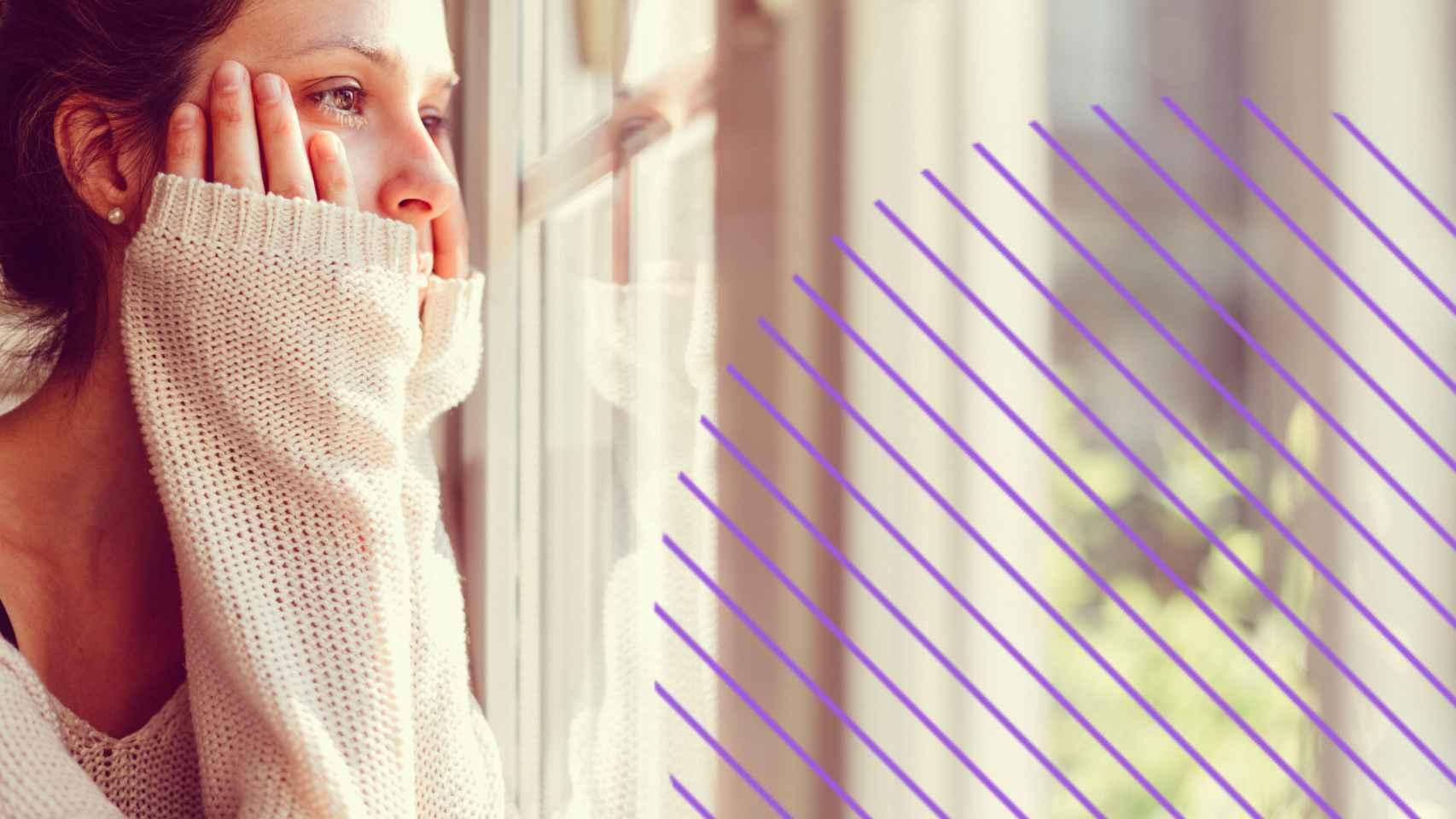 Una mujer mirando por la ventana.
