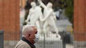Un hombre protegido con una mascarilla transita una calle del madrileño barrio de Malasaña.