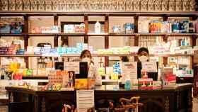 Mari Luz y Cristina tras el mostrador de la Farmacia de la Reina Madre, en Madrid.