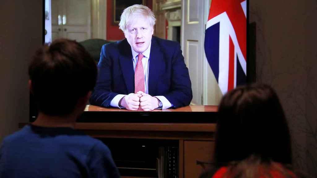 Ciudadanos británicos ven el discurso televisado de Boris Johnson, este lunes.