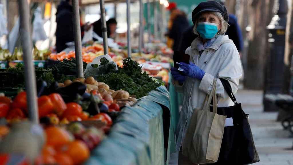 Una mujer en el mercado con mascarilla.
