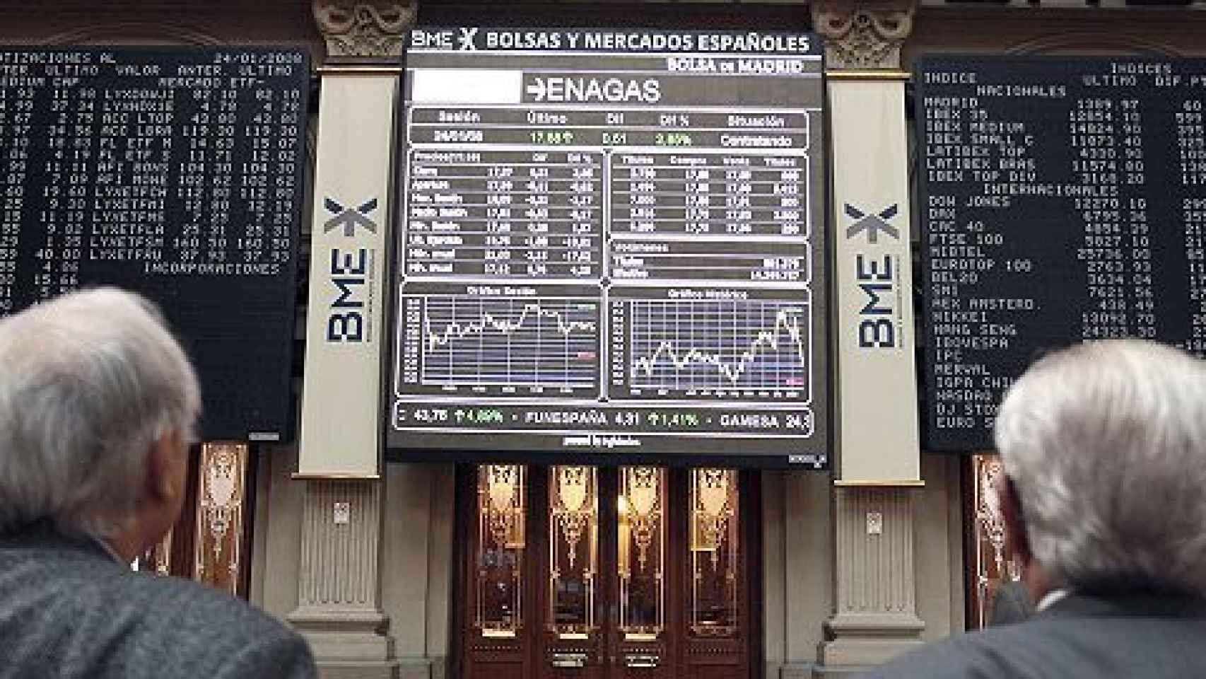 Dos hombres observan pantallas de negociación en la Bolsa de Madrid.