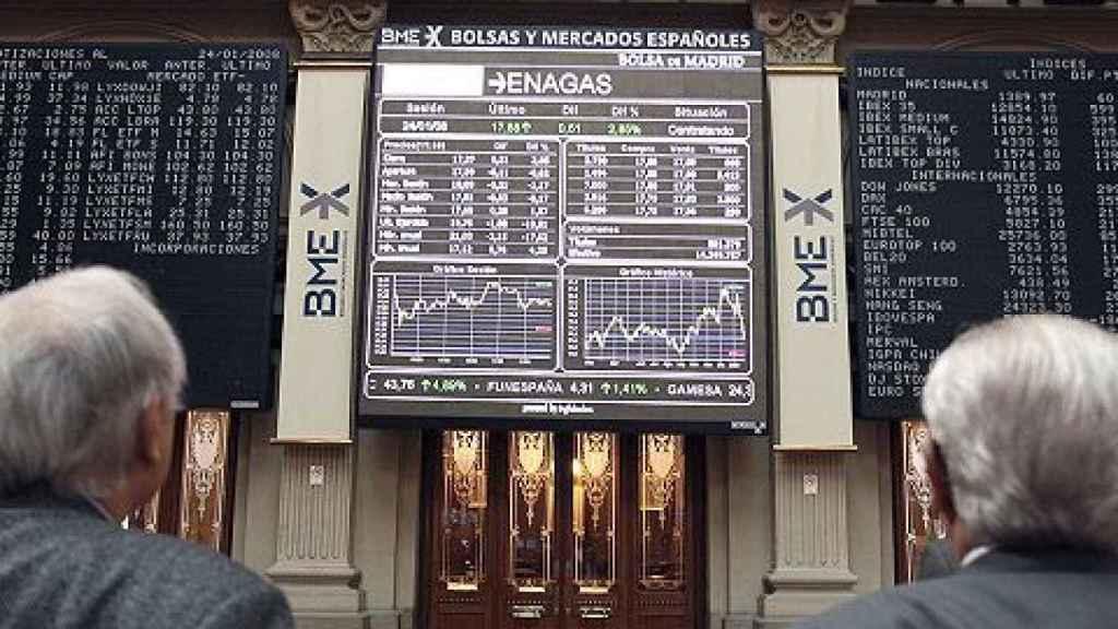 Dos inversores miran pantallas de cotización en la Bolsa de Madrid.