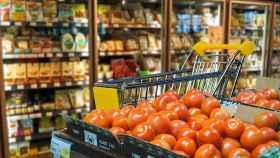 Un supermercado con varias neveras de productos en el fondo.
