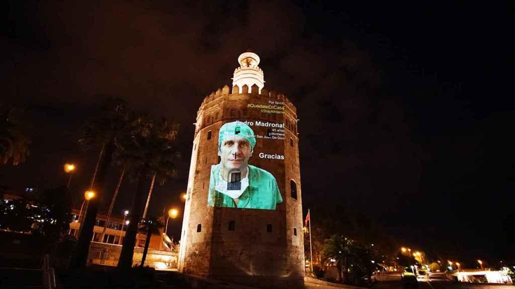 La imagen de un sanitario proyectada sobre la Torre del Oro.