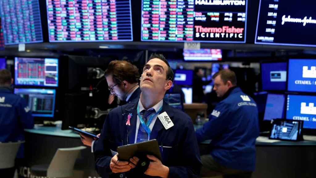 Un bróker consulta pantallas de negociación en Wall Street.