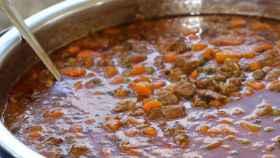 Una olla con un guiso de carne y zanahorias.