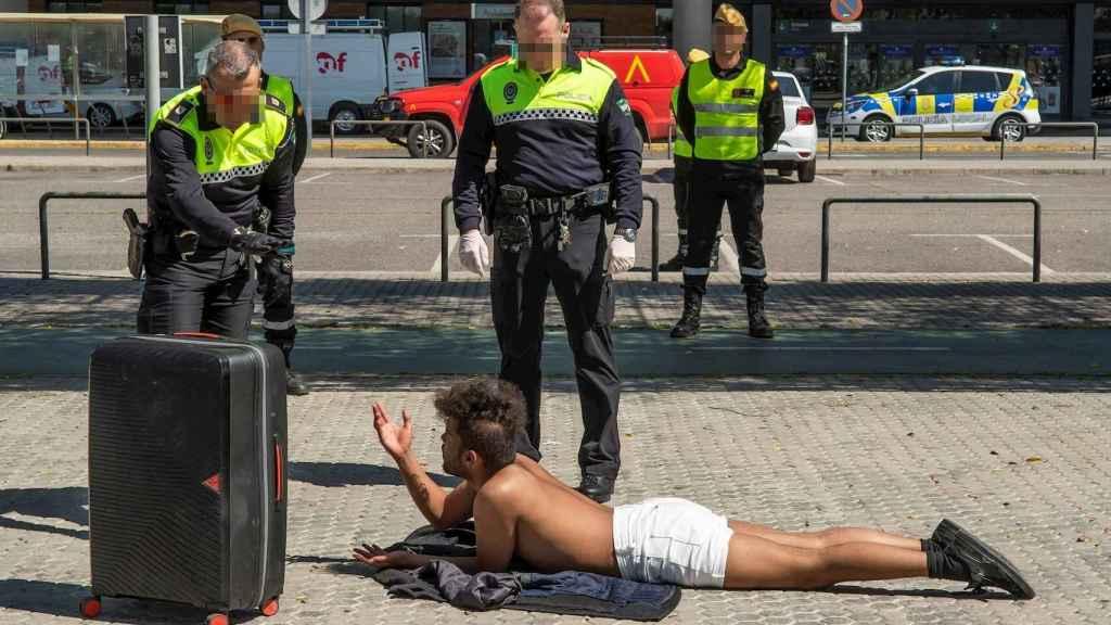 La Policía Local llama la atención a un 'sin techo' belga que toma el sol junto a la estación de Santa Justa. EFE/ Raúl Caro.