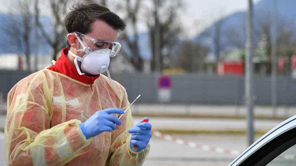 Un sanitario se dispone a tomar una muestra para un test de coronavirus.