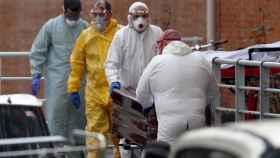 Trabajadores de una funeraria protegidos trasladan de la morgue a un fallecido por coronavirus.