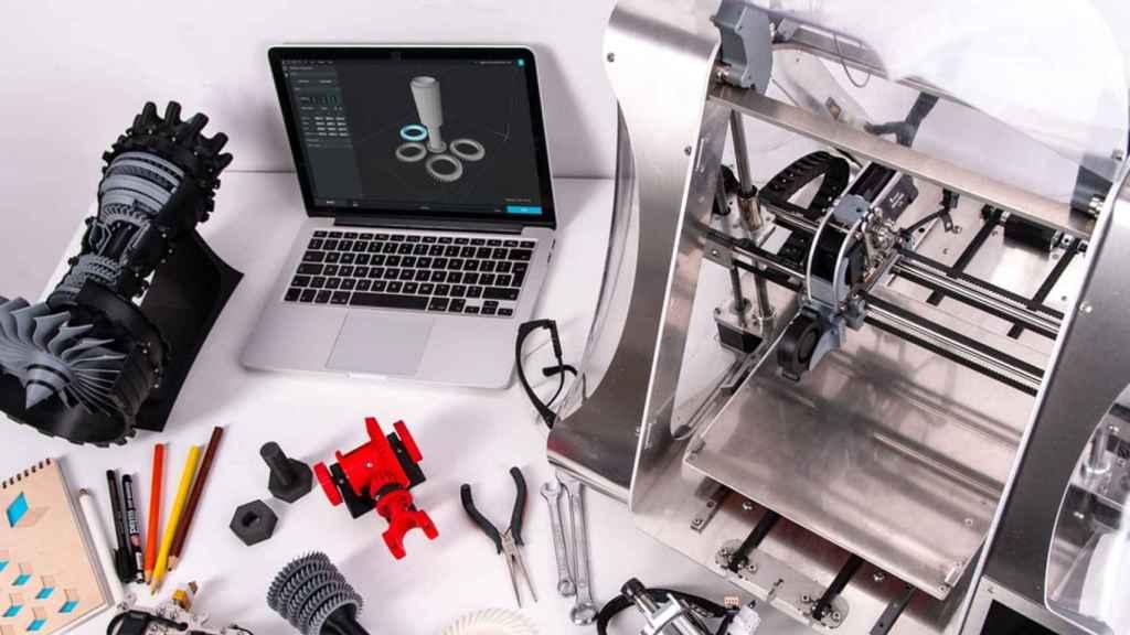 Impresora 3D junto a algunos objetos de su creación.