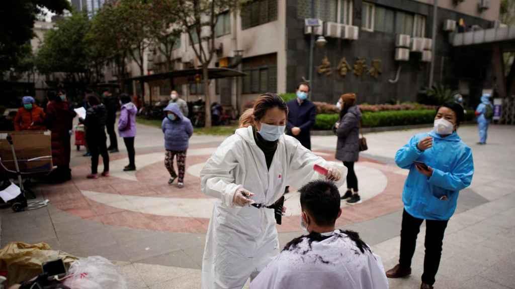 Una persona corta el pelo a otra en la ciudad de Wuhan.
