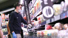 Varias personas hacen la compra con mascarilla y guantes en un supermercado en Madrid durante el confinamiento.