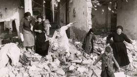 Una familia de Vallecas, en su casa derruida por las bombas.