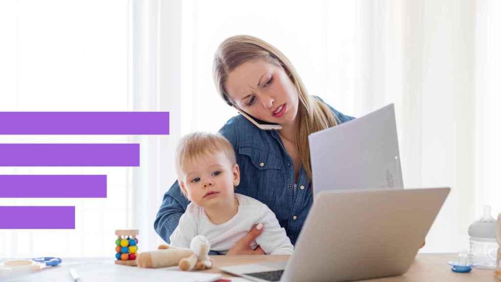 Una mujer trabajando y cuidando a su hijo.