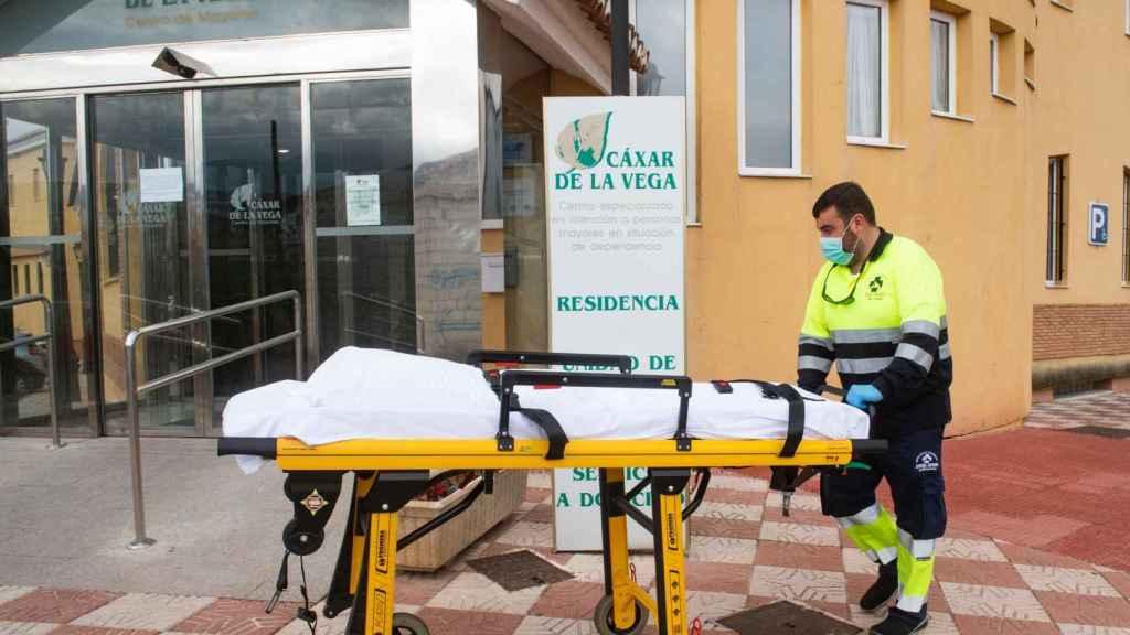 Personal sanitario traslada una camilla en la residencia de mayores de Cájar (Granada) donde varios ancianos han fallecido en los últimos días.