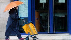 Una cartera, protegida con mascarilla, reparte el correo bajo la lluvia, este martes en Valencia.