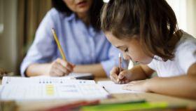 Una madre y su hija haciendo deberes de la escuela.