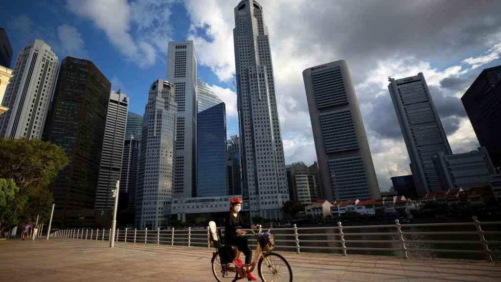 Un ciclista frente al área del Distrito Central de Negocios (CBD) en Singapur, 03 de abril de 2020.