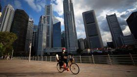 Una ciclista frente al área del Distrito Central de Negocios (CBD) en Singapur.