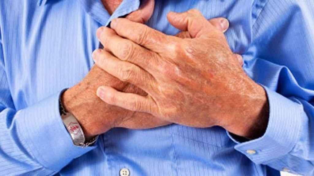 Un hombre se lleva la mano al pecho durante un infarto.