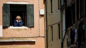Una mujer se asoma a la ventana en su confinamiento en Venecia.