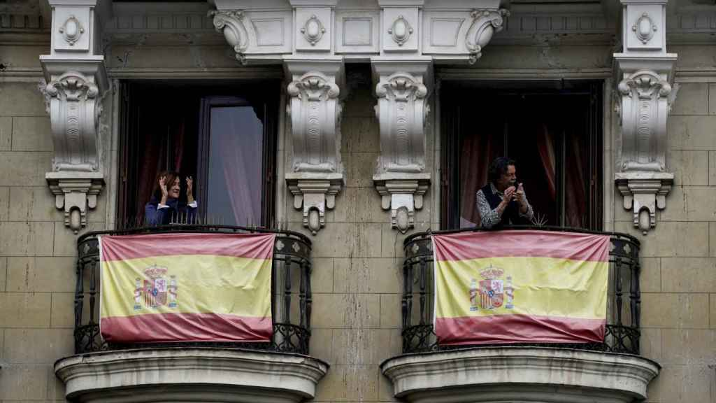 Dos ciudadanos aplauden desde los balcones de sus casas, en Madrid.