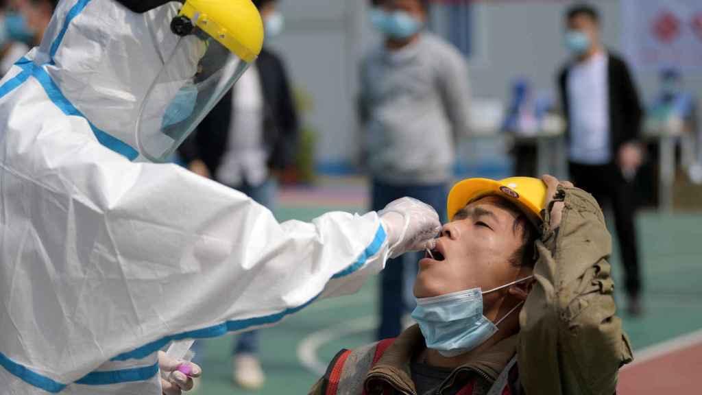 Test de coronavirus practicado a un trabajador, en Wuhan.