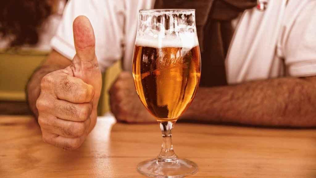 Un hombre contento por tomarse una cerveza.