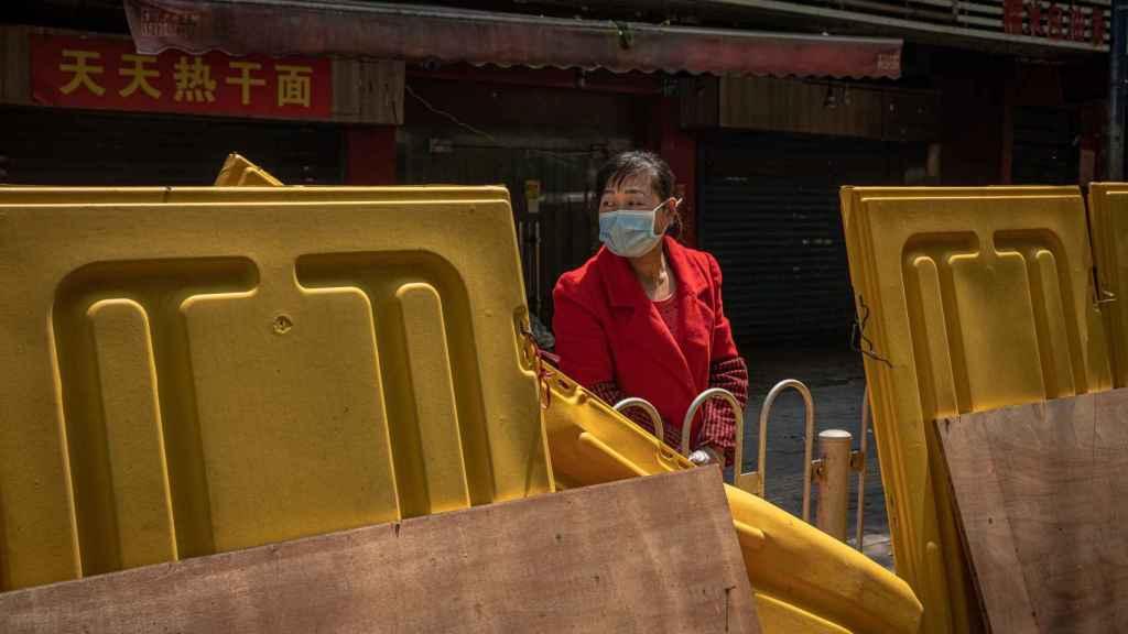 Una ciudadana de Wuhan, tras una de las vallas que se situaron entre barrios.