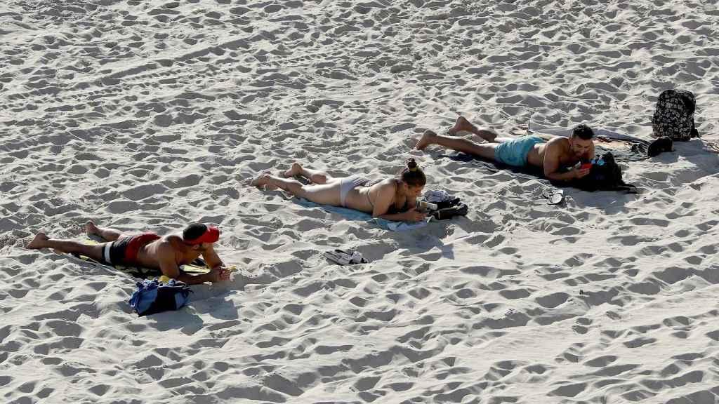 Bañistas toman el sol mientras mantienen la distancia de seguridad en Perth, Australia. EFE/EPA Richard Wainwaight