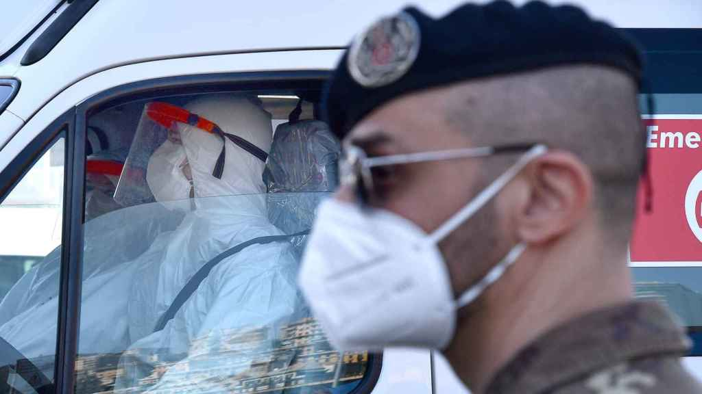 Un soldado frente a trabajadores sanitarios con mascarilla en Génova
