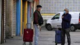 Dos hombres conversan manteniendo las distancias a las puertas del Mercado Central de València. EFE/Manuel Bruque