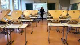 Una profesora da clases virtuales ante un aula vacía.